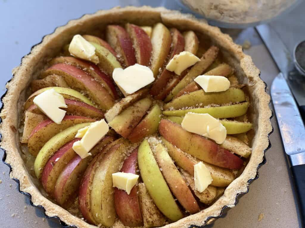 Sliced apples in an apple tart with chunks of butter on the top