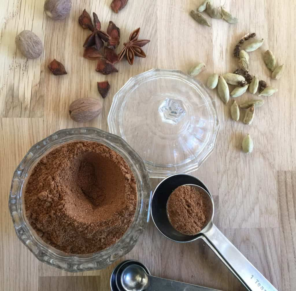 Spice mix in a small glass jar with a measuring spoon on the side.