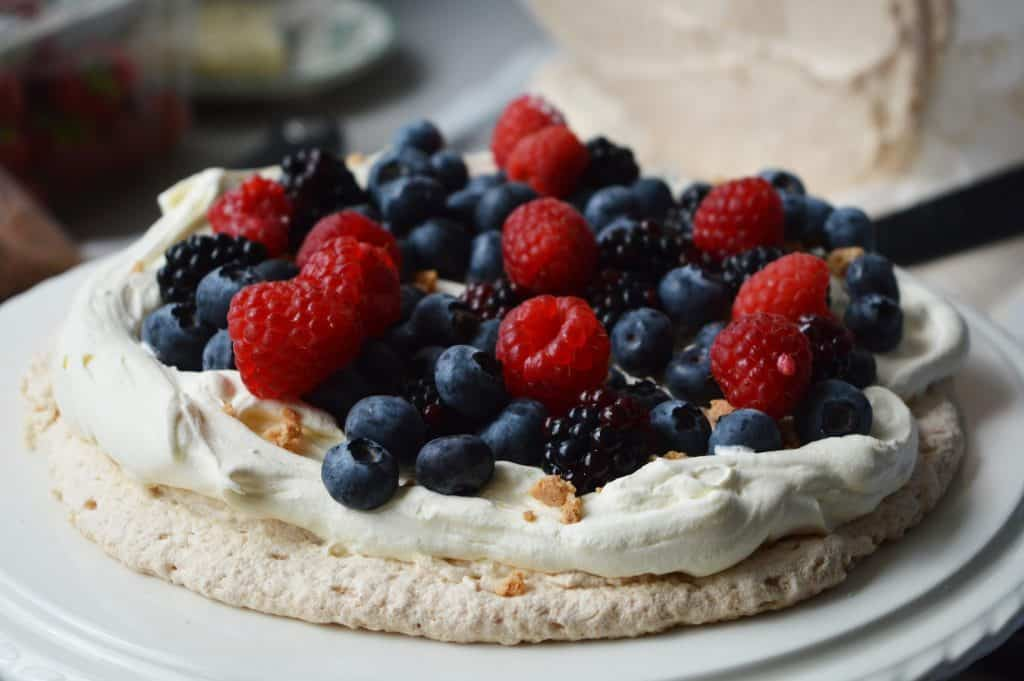 meringue layer with cream and berries on a white cake stand