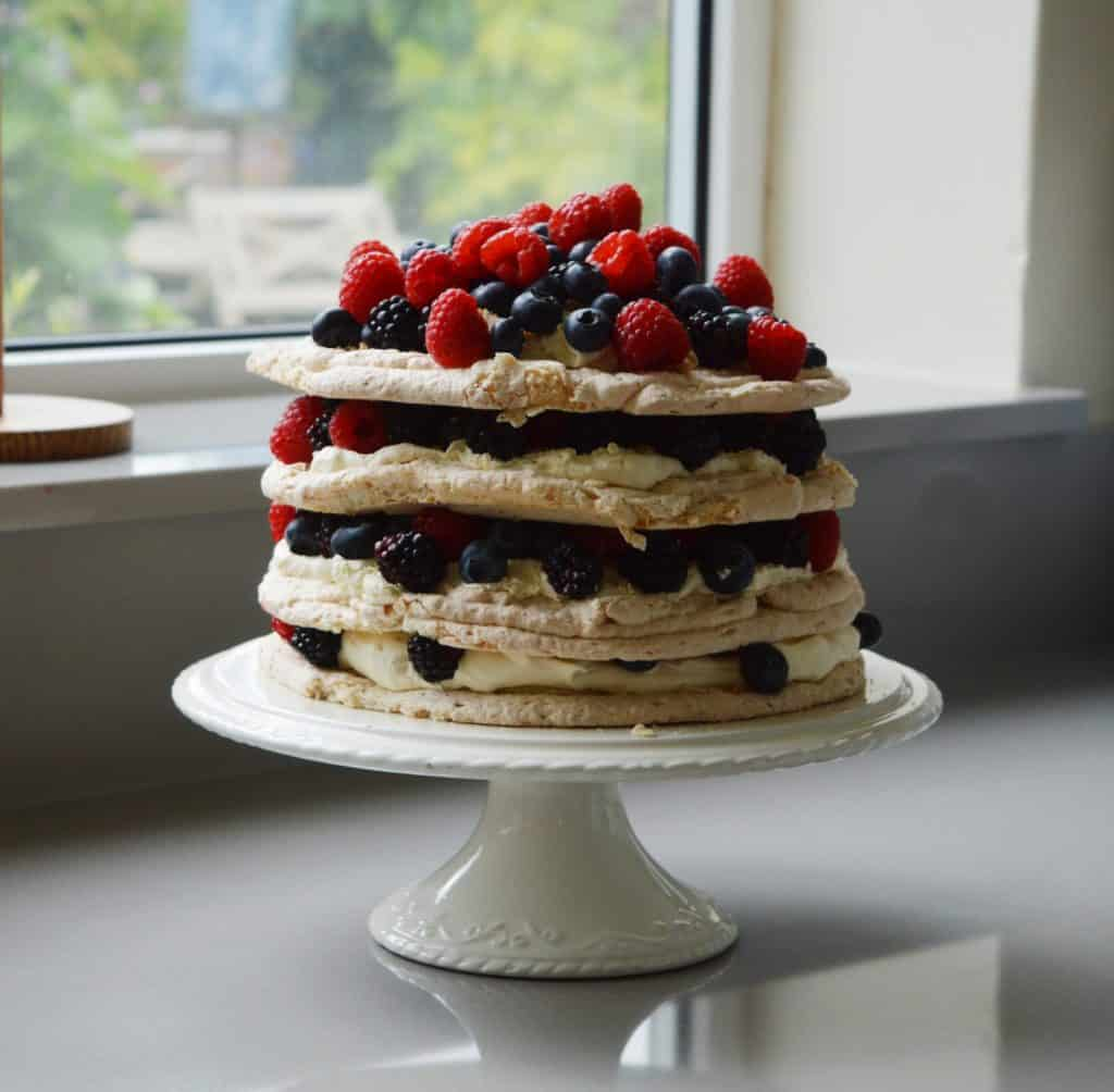 4 layers of meringue with fruit on a white cake stand.
