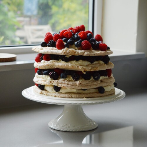 Layers of meringue fruit and cream on a white cake stand