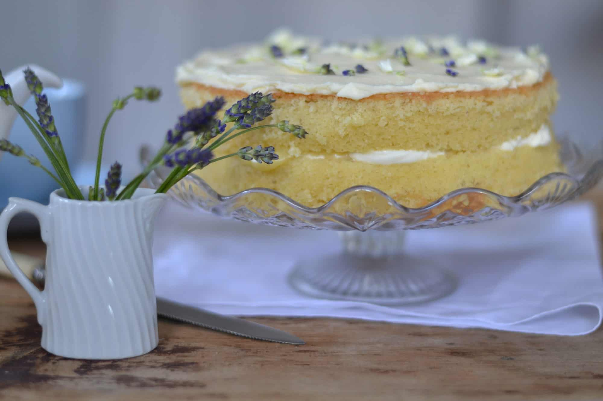 Cake on a cake stand with a jug of flowers