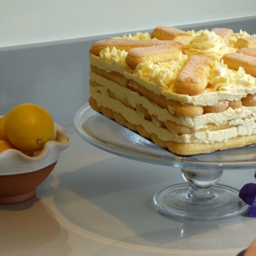 Lemon sponge fingers icebox cake on a glass cake stand