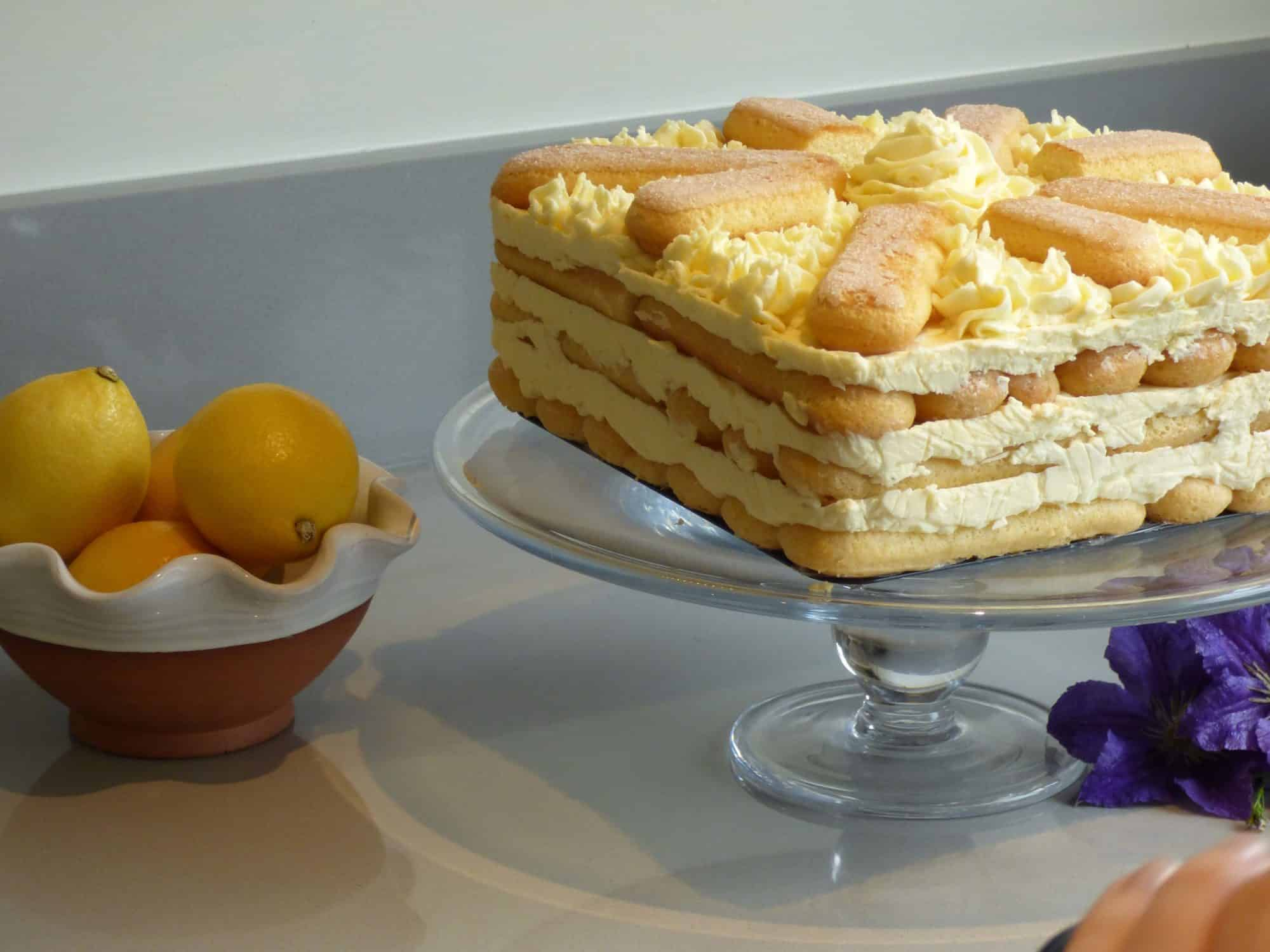 Lemon sponge fingers icebox cake on a glass cake stand
