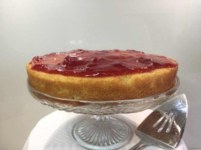 Layer of jam and sponge cake on a glass cake stand