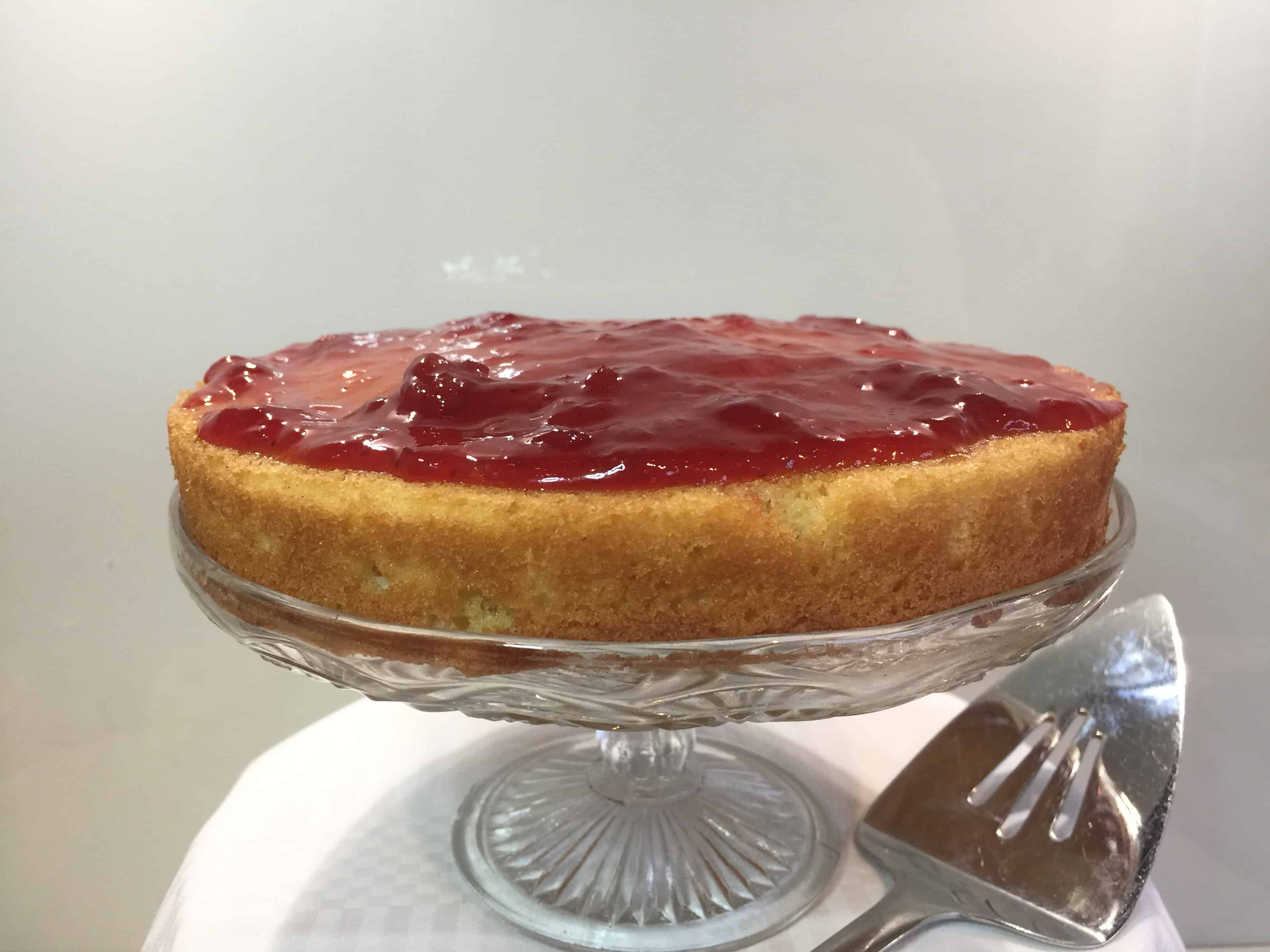 Layer of jam and sponge cake on a glass cake stand is the basis for classic victoria sandwich cake