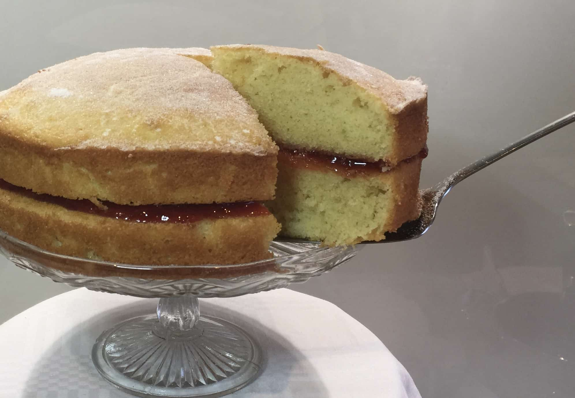victoria sandwich on a glass cake stand with a serving knife