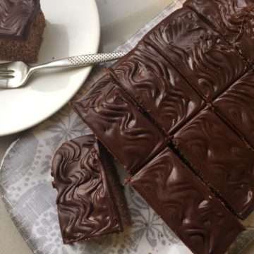Chocolate cake on a grey patterned tray. With a slice of cake on a white plate.