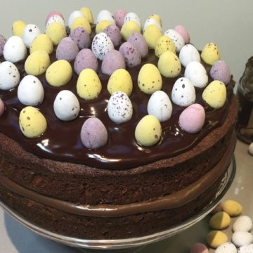 Chocolate Cake Decorated with sugar coated eggs. On a glass cake stand.