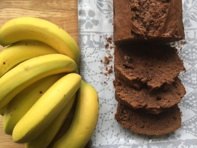 Banana and Chocolate Loaf with a bunch of bananas on a serving plate.