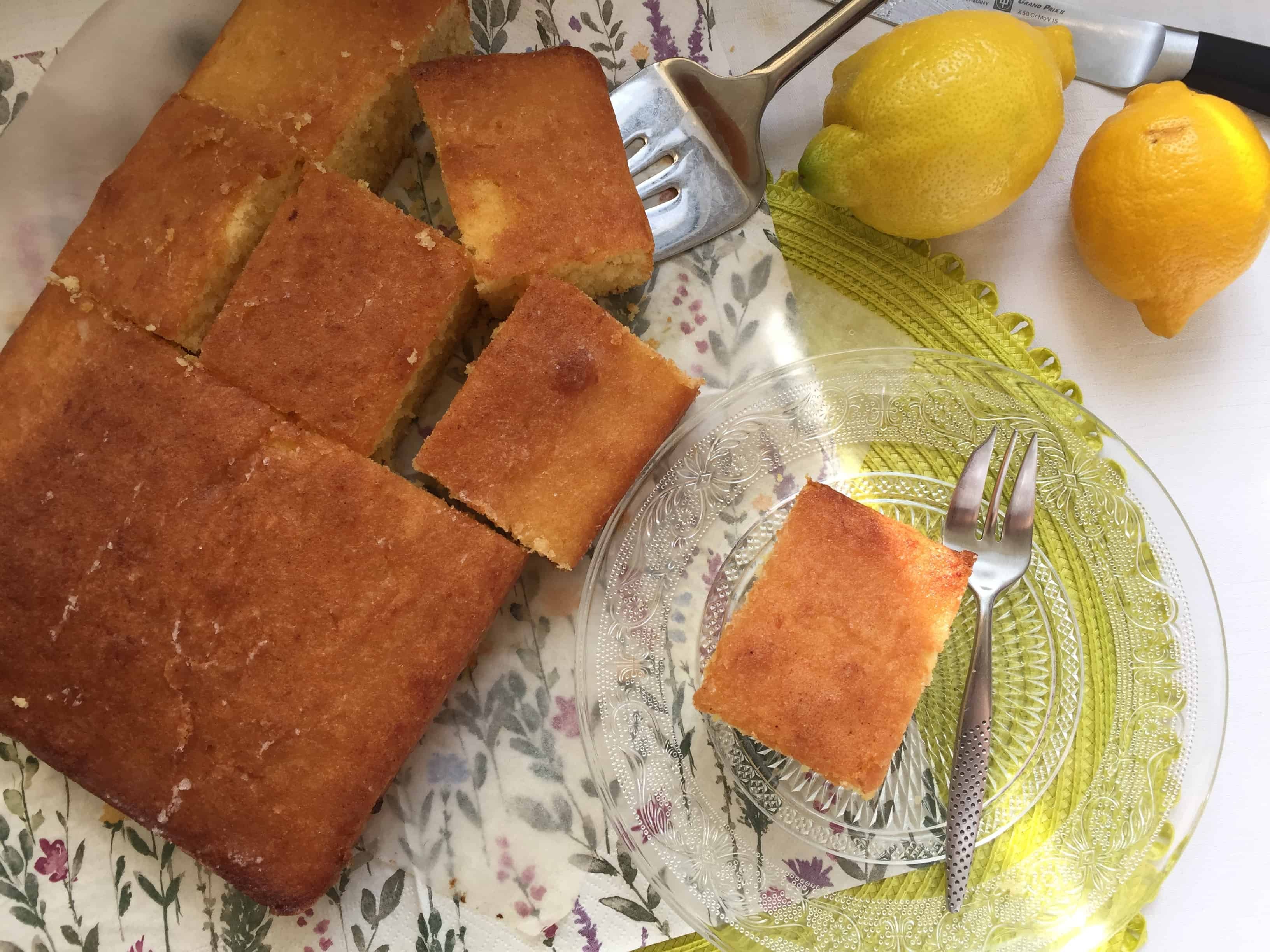 Slices of cake with lemons on the side.
