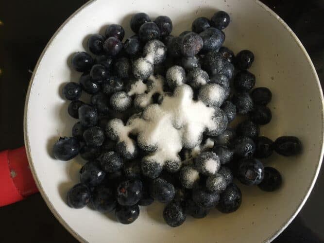 Blueberries sugar and water in a small shallow pan.