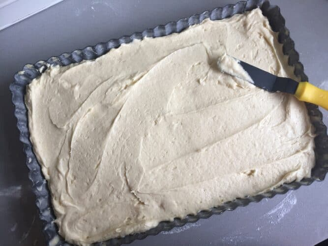overhead shot of vanilla sheet cake batter being spread evenly into the cake tin.