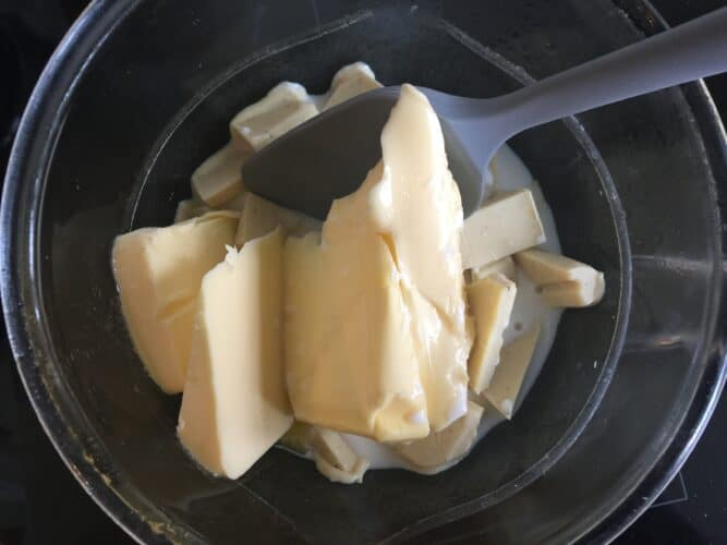overhead shot of white chocolate, butter and milk in a glass bowl over a pan of simmering water.