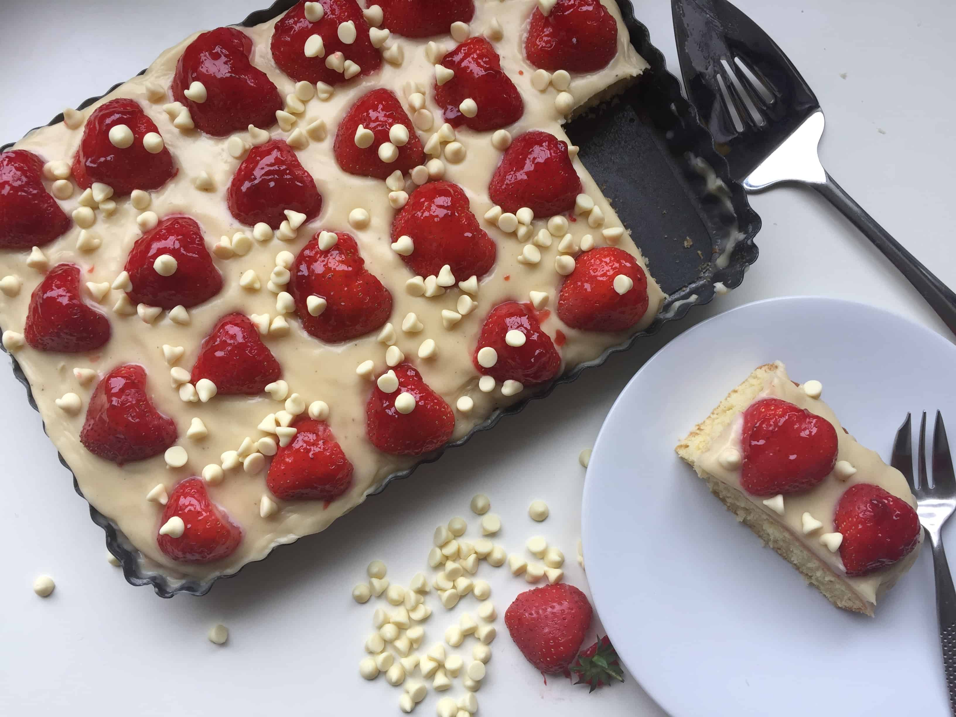 overhead shot of vanilla sheet cake topped with a white chocolate frosting, fresh strawberries and white chocolate chips.