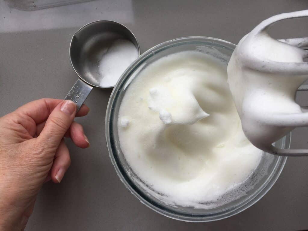 Whisked egg whites in a glass bowl.