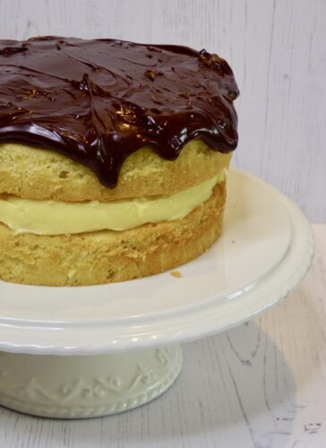 boston cream pie on a white cake stand