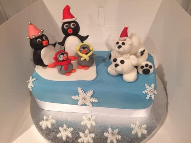 Cake with Fondant cake toppers shaped like penguins and polar bears wearing santa hats