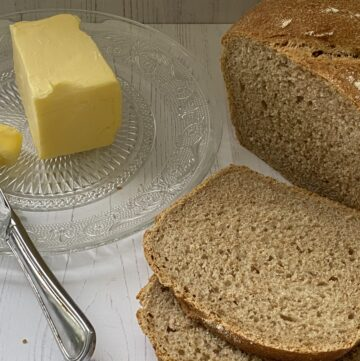 Butter on a glass plate. Slices of brown bread