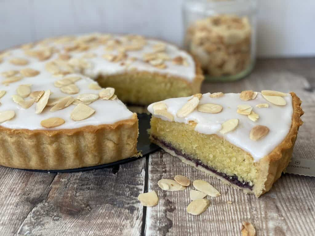 Slice of Bakewell Tart with a jar of toasted alomonds