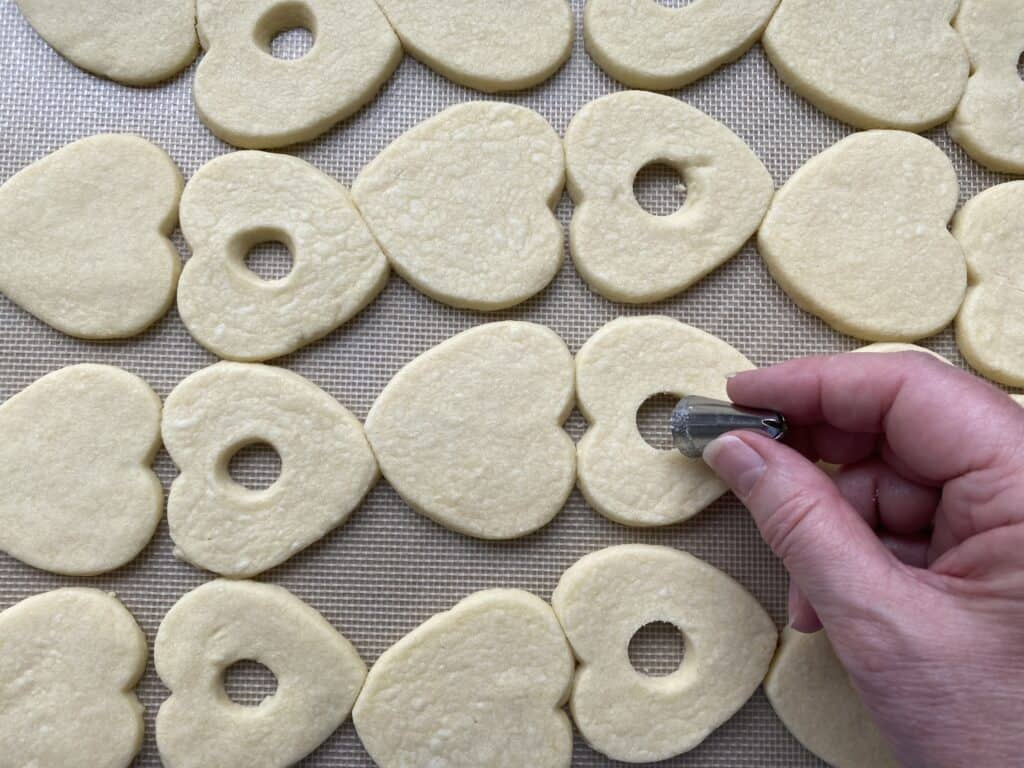 baked biscuit cut outs on a sheet of baking parchment