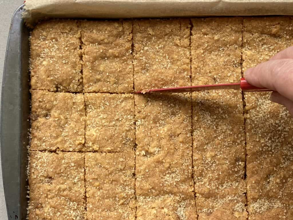 Slicing Cookie bars with a red knife