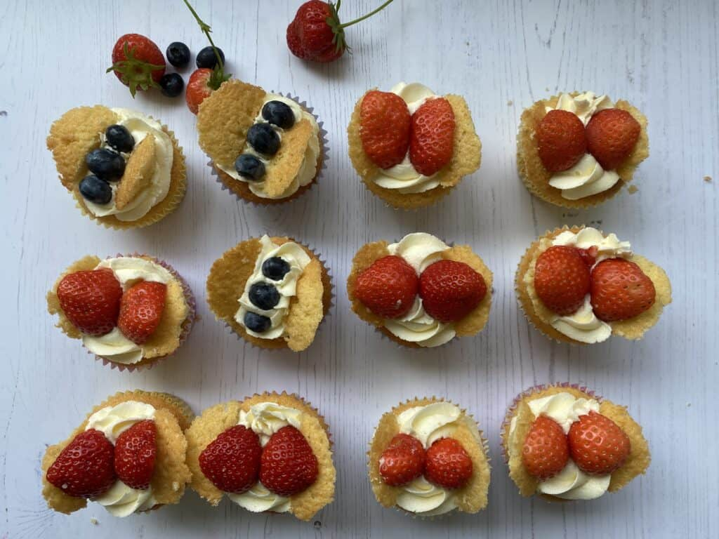 Rows of small cakes with buttercream and fruit on the top