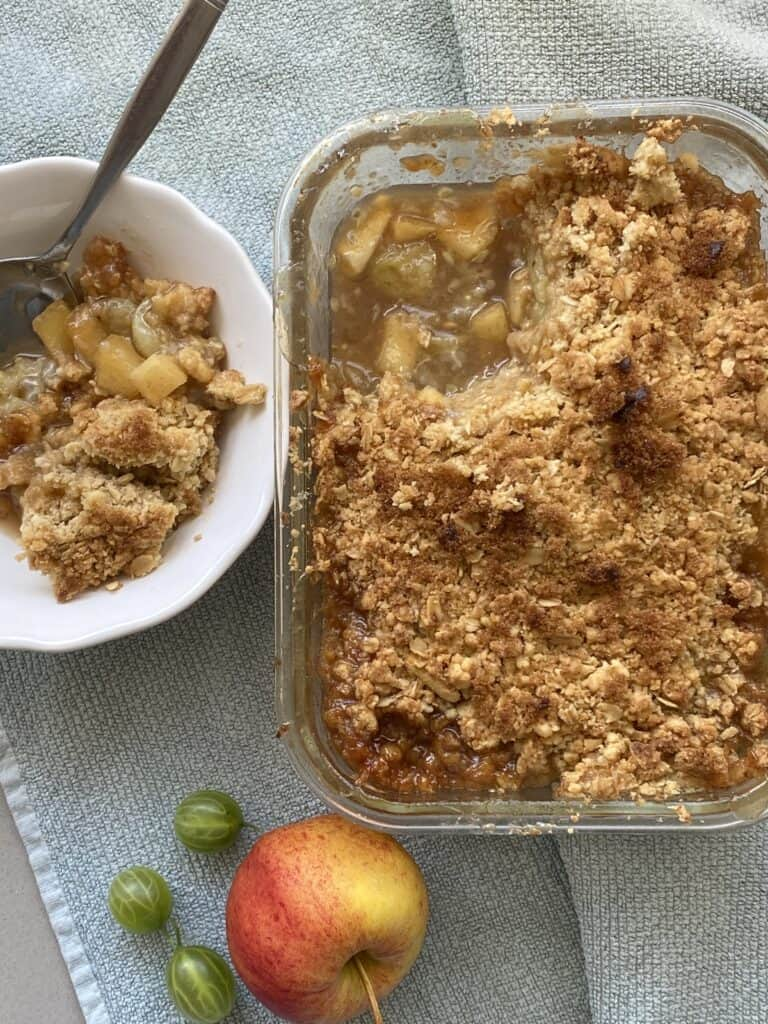 Gooseberry and Apple Crumble in a clear dish. Portion served in a white dish