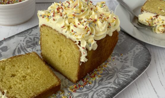 Vanilla Loaf cake with a slice cut out on a grey plate.