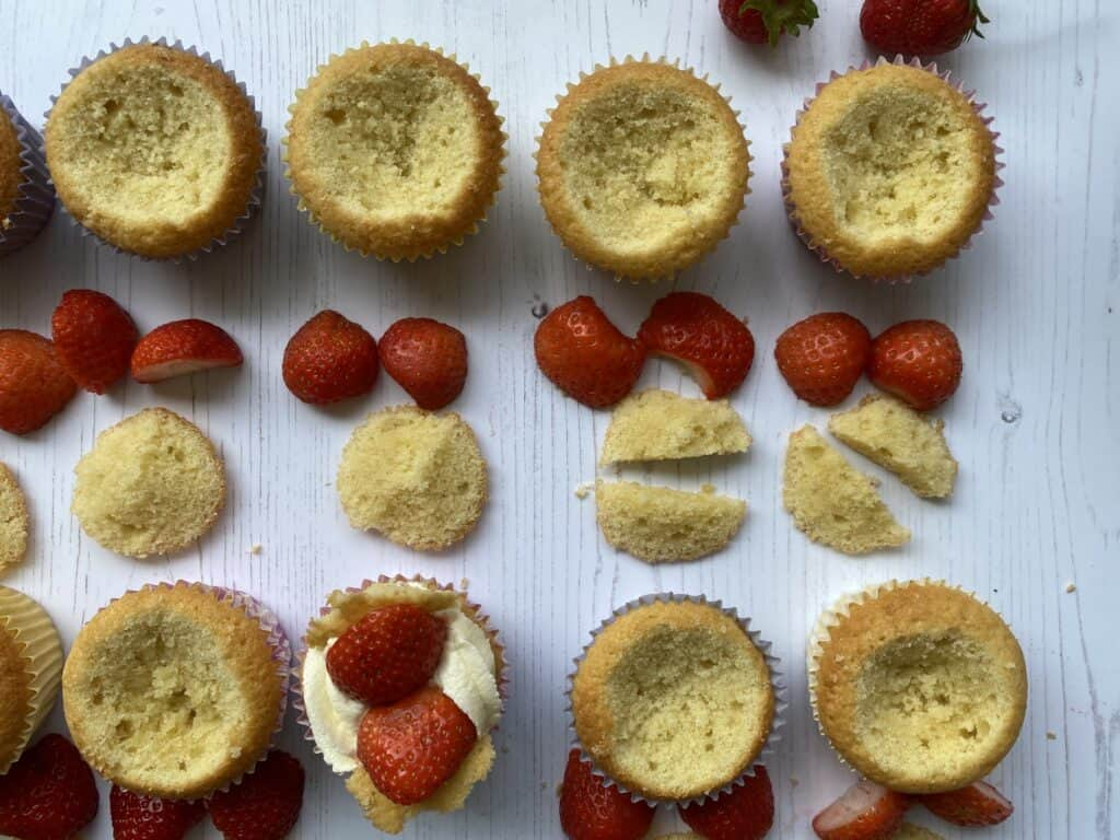 Rows of strawberry butterfly buns with slices of strawberries