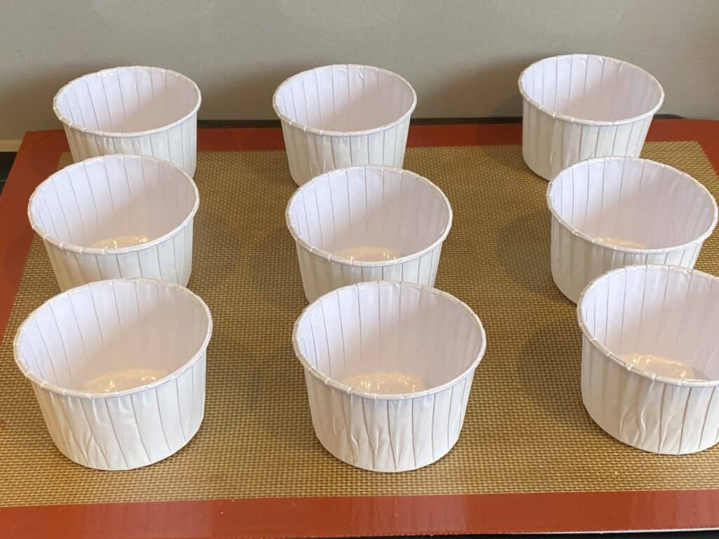 9 white paper muffin cases on a baking tray