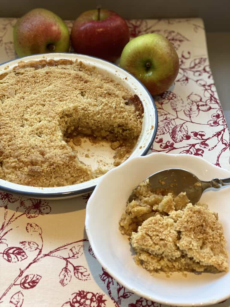Apple Crumble with a portion served in a white dish.