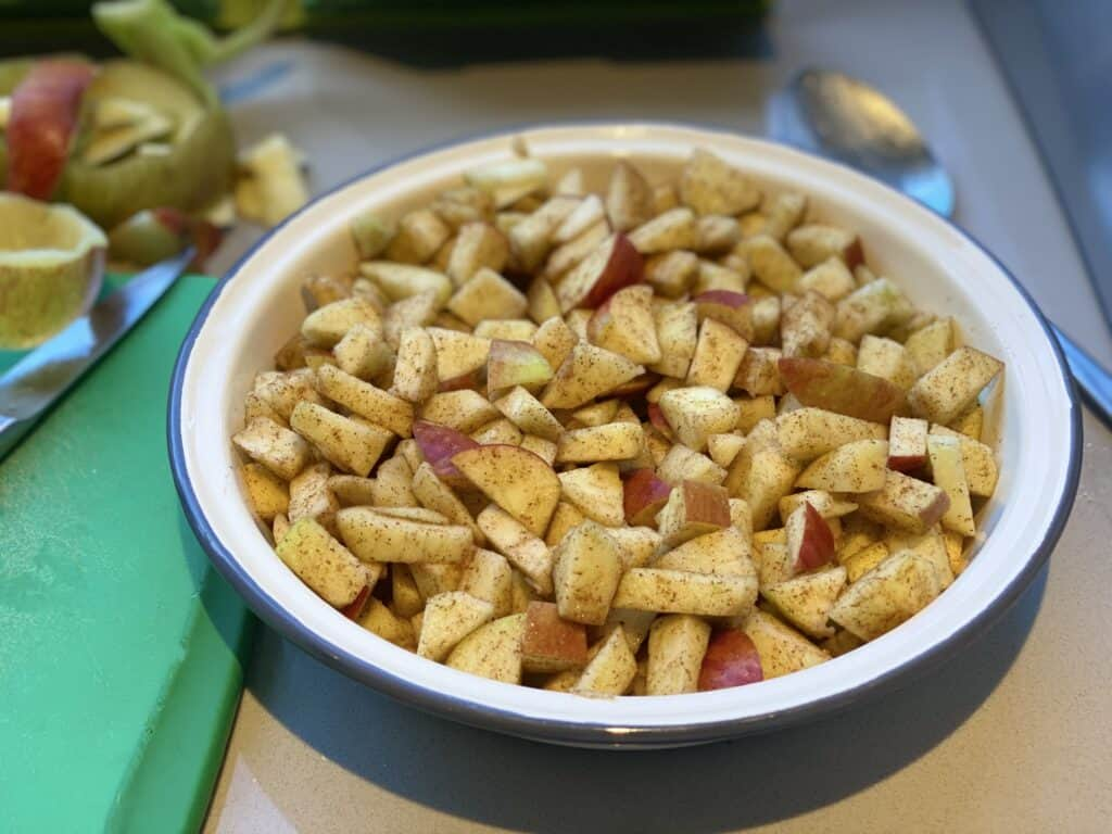 Chopped apples coated in spice placed in a pie dish