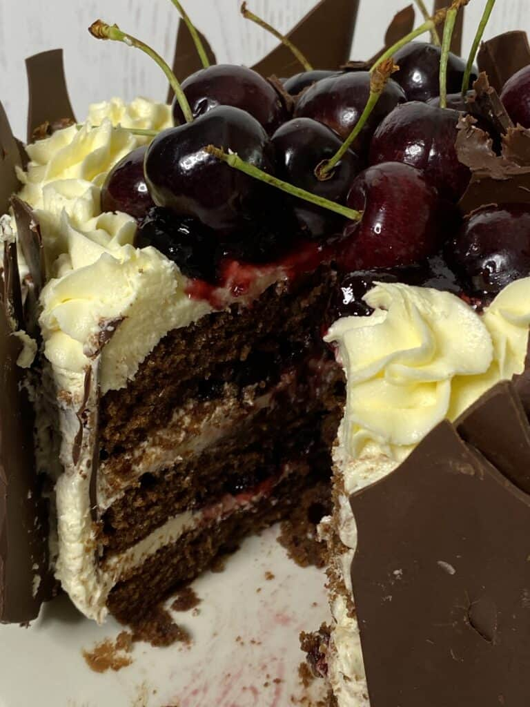 Cherry Black Forest cake with a slice cut out.