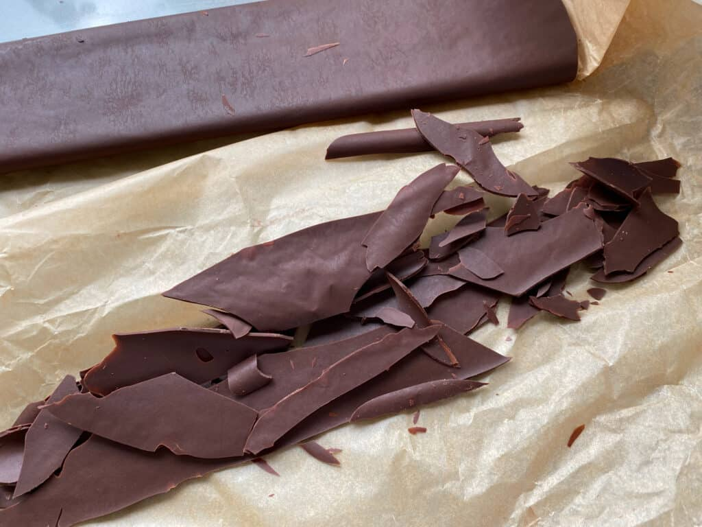 Chocolate shards on a sheet of baking parchment