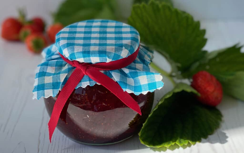 Jar of jam with a blue fabric lid.