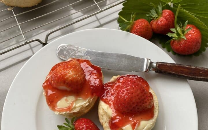 Sweet scones with butter and jam on a white plate